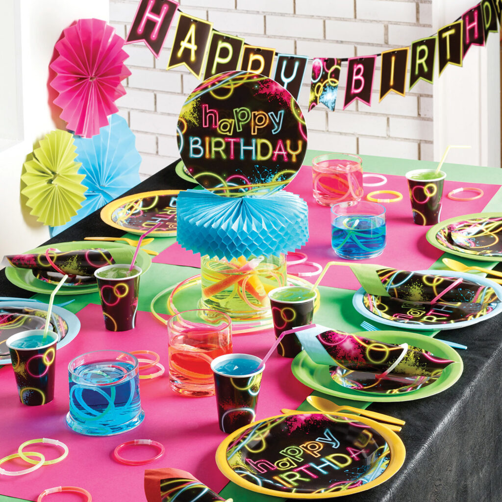 Neon glow stick colors on black background on plates cups and decorations