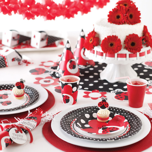 red gerbera daisies on polka dot and ladybugs on plates napkins tablecloth and decorations