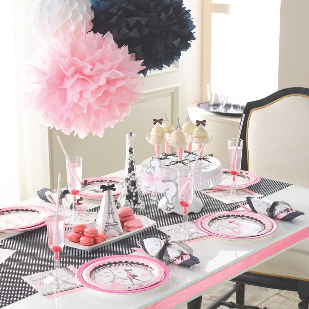 Pink and black and white with Eiffel Tower and lady in pink with plates napkins and table cloth and elegant decorations